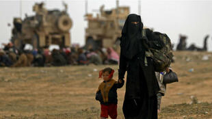 Une femme et son enfant quittent la ville de Baghouz, dernier bastien de l'organisation État islamique en Syrie, le 13 février 2019.