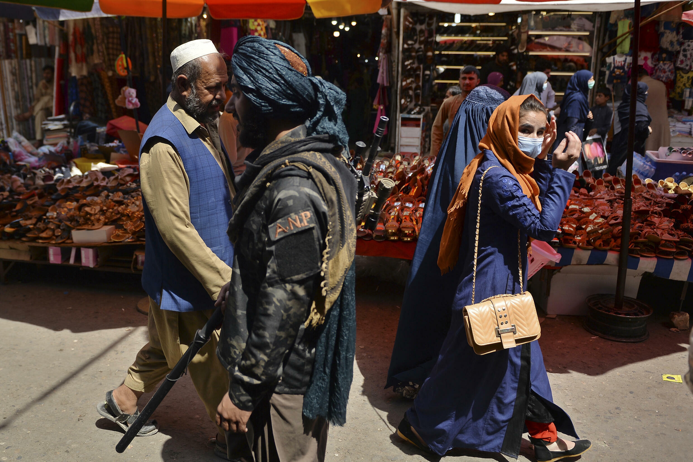 مقاتل من طالبان (وسط) يمر قرب متسوقين في سوق منداوي في كابول في 1 أيلول/سبتمبر 2021.