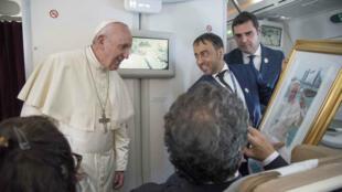 El papa Francisco recibe un regalo de un periodista durante una sesión de preguntas después de su visita a Abu Dhabi, Emiratos Árabes Unidos, el 5 de febrero de 2019.