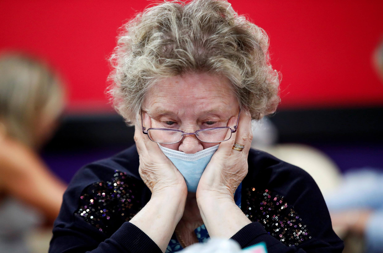 سيدة ترتدي كمامة وهي تلعب لعبة البينغو بعد إعادة فتح صالة لعب كانت قد أغلقت بسبب تفشي مرض فيروس كورونا في لوتون بريطانيا، 4 يوليو/تموز 2020.