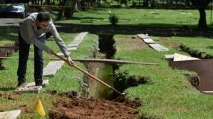 """خبيرة في الطب الشرعي في مقبرة """"حديقة لاباز"""" في العاصمة البنمية تقوم بانتشال رفات ضحايا للغزو الأميركي لبنما في 1989، في 11 حزيران/يونيو 2020"""