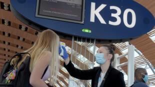 Prise de température avant de monter dans un vol Air France, à l'aéroport Roissy-Charles de Gaulle, le 12 mai 2020