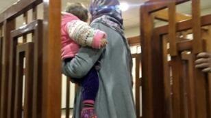 الجهادية الفرنسية ملينا بوغدير تحمل ابنها لدى وصولها إلى المحكمة في بغداد في 19 شباط/فبراير 2018