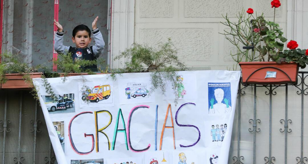 Un niño aplaude desde el balcón de su casa en apoyo de los trabajadores de la salud, frente al Hospital Dos de Maig, durante el brote de coronavirus en Barcelona, España, el 11 de abril de 2020.