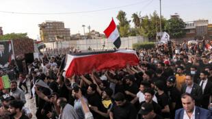 مشيّعون يطلقون هتافات في جنازة الناشط المناهض للحكومة إيهاب الوزني في كربلاء في 9 أيار/مايو 2021.