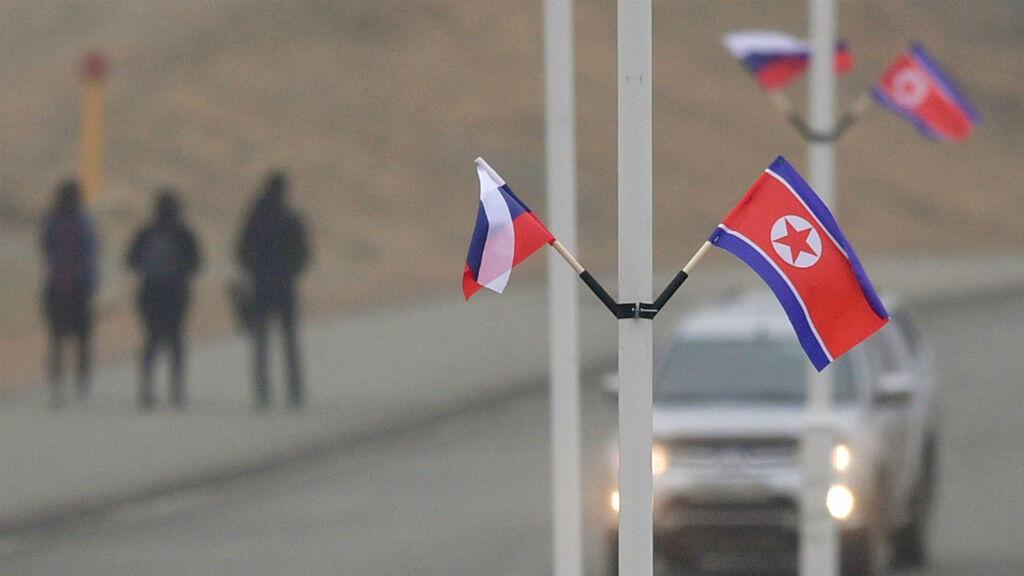 Las banderas de Rusia y Corea del Norte se ven fijas en las farolas de la isla Russky en el puerto ruso de Vladivostok, en el extremo oriental de Rusia, el 23 de abril de 2019.