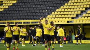 L'attaquant norvégien de Dortmund, Erling Braut Haaland (c), exulte après la victoire de son équipe face à Schalke lors du premier match de reprise de la Bundesliga, à Dortmund, le 16 mai 2020