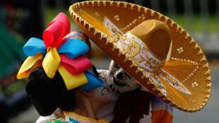 Una pareja vestida como Catrina y Catrin se besan en medio de un desfile conmemorativo del día de los muertos. México, Octubre 28, 2017