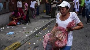 La gente recolecta vegetales luego de que un mercado callejero fuera saqueado en el vecindario de Chacao en Caracas el diez de marzo de 2019, durante el cuarto día de un apagón masivo que dejó a los venezolanos sin comunicaciones, electricidad y agua.