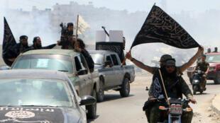 Des combattants du Front al-Nosra paradent le 26 mai 2015 aux alentours d'Alep avec des drapeaux de groupes jihadistes.