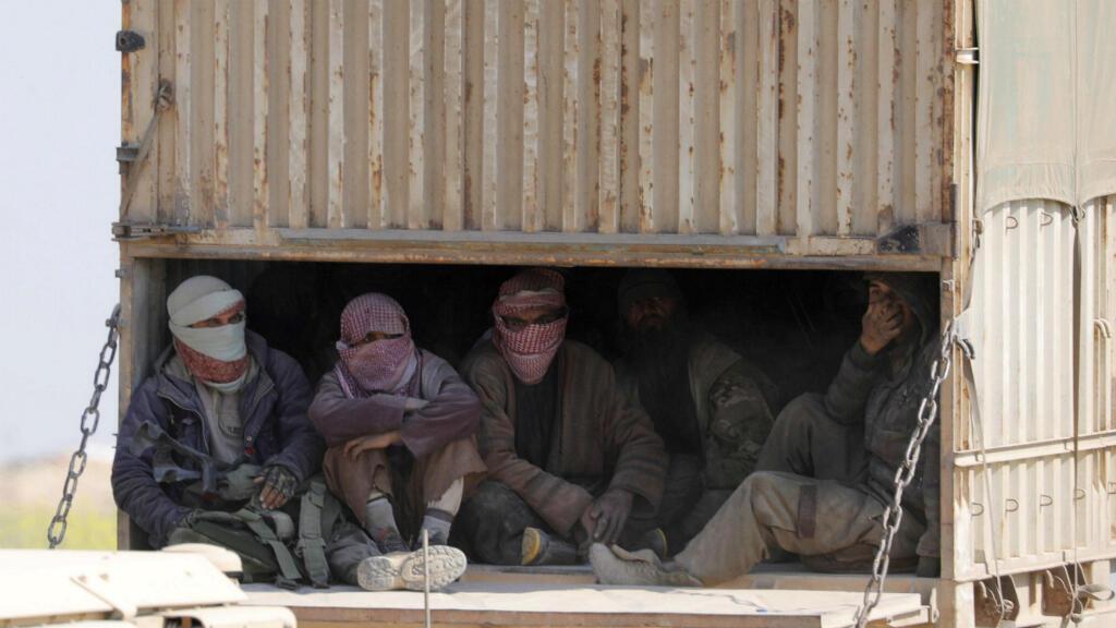 Hombres con rostros cubiertos se sientan en la parte trasera de un camión cerca de la aldea de Baghouz, provincia de Deir Al Zor, Siria, el 20 de febrero de 2019.