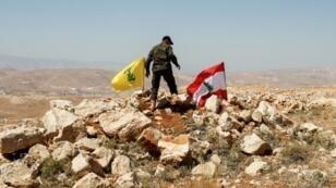 مقاتل يرفع العلم اللبناني وراية الحزب في إحدى تلال منطقة عرسال في البقاع اللبناني