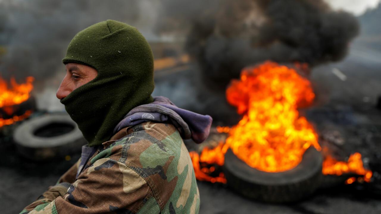 Un manifestante se encuentra junto a  una barricada en llamas en medio de las protestas después de que el Gobierno del presidente de Ecuador, Lenín Moreno, terminara con los subsidios al combustible vigentes durante cuatro décadas, cerca de Machachi, Ecuador, el 7 de octubre de 2019.