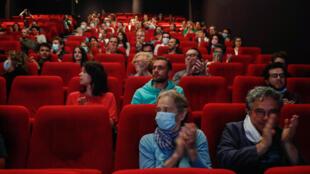 """Des spectateurs applaudissent avant la projection du film """"Les Parfums"""", le 21 juin 2020 à Paris, suite à la réouverture des salles de cinéma avec l'assouplissement des mesures de confinement."""