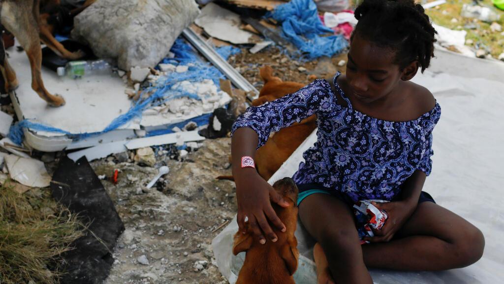 Una niña acaricia a su perro después de que el huracán Dorian azotara las islas Ábaco en Spring City, Bahamas, el 11 de septiembre de 2019.