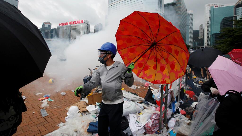 Un manifestante sostiene una sombrilla en medio de los enfrentamientos con la policía de Hong Kong el 12 de junio de 2019. Las protestas se oponen a un proyecto de ley que permitiría la extradición de personas requeridas por China desde el distrito autónomo.