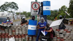 Manifestantes se paran en una barricada durante una protesta contra el gobierno del presidente nicaragüense Daniel Ortega en Nindiri, Nicaragua, el 5 de junio de 2018.