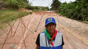 Un indígena se encuentra en una barricada que bloquea la carretera panamericana durante una protesta para exigir al gobierno el cumplimiento de varios acuerdos sobre territorio, democracia, justicia, seguridad y paz en Mondomo, Departamento del Cauca, Colombia, el 17 de marzo de 2019.