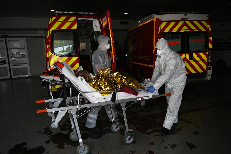 Des marins-pompiers de Marseille en tenue de protection contre le Covid-19 transporte à l'hôpital une femme suspectée d'être infectée par le virus, le 15 avril 2020.