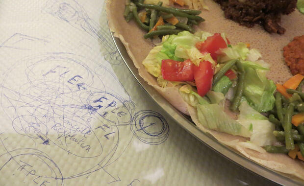 Said Ali,a well-known member of Paris' small Eritrean community, sketched out Eritrea's troubled post-independence political history, which has led to thousands of refugees, on the tablecloth at the Eritrean restaurant where he works. (photo: Brenna Daldorph)