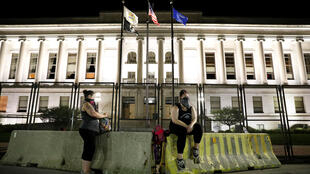 Women rest at a barricade in front of the Kenosha County Courthouse following the police shooting of Jacob Blake, a Black man, in Kenosha, Wisconsin, August 26, 2020.