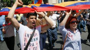 Manifestantes opositores al gobierno en Armenia sostienen la bandera de su país durante una marcha el 26 de abril de 2018.