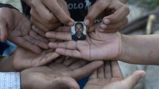 La salvadoreña Rebeca Valle de Barrera (D) y sus cinco hijos muestran una foto de su difunto esposo Joaquín Barrera quien, junto con sus padres y otros dos hermanos, falleció recientemente a causa de COVID-19, en su casa de Santiago Nonualco, departamento de La Paz, El Salvador, el 23 de julio de 2020.