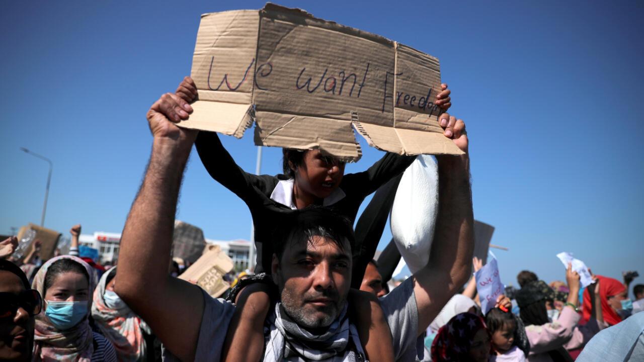 Un hombre sostiene a un niño cuando refugiados y migrantes del campamento destruido de Moria protestan pidiendo irse después de la noticia sobre la creación de un nuevo campamento temporal en la isla de Lesbos, Grecia, el 11 de septiembre de 2020.