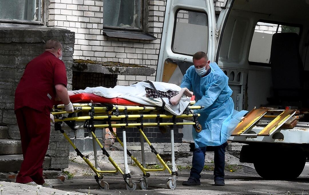 Dos enfermeros llevan a un paciente al Hospital de Botkin, el principal centro de tratamiento de Covid-19 de San Petersburgo el 3 de junio de 2020.