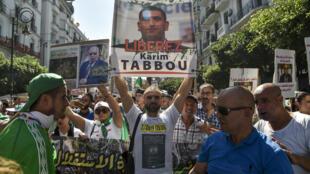 متظاهرون جزائريون يرفعون صورة الناشط كريم طابو في 27 أيلول/سبتمبر 2019 في العاصمة