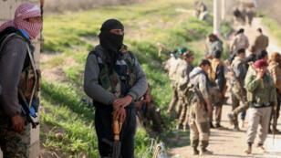 Les combattants des Forces démocratiques syriennes (FDS) soutenues par les États-Unis se reposent dans le village syrien en première ligne à Baghouz, le 18 février 2018.