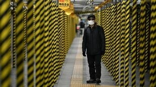 A man wearing a face mask walks between columns at a subway station being renovated in Seoul on February 22, 2020. - South Korea reported 142 more coronavirus cases on February 22, the sharpest spike in infections yet, with more than half of the new cases linked to a hospital in a southern city. The national toll of 346 is now the second-highest outside of China. (Photo by Jung Yeon-je / AFP)