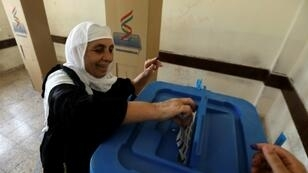 An Iraqi Kurdish woman casts her ballot for the parliamentary election at a polling station in Arbil, the capital of the Kurdish autonomous region, on September 30, 2018