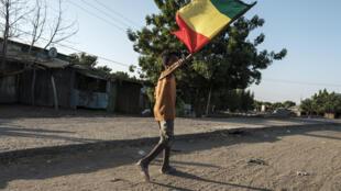 Un garçon marche avec un drapeau éthiopien dans une rue de Mai Kadra, en Éthiopie, le 21 novembre 2020.