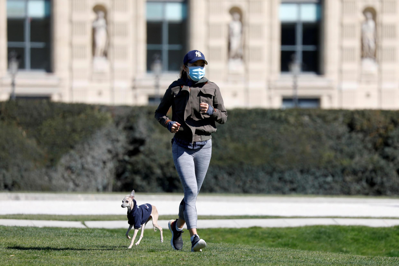Une femme fait un jogging avec son chien pendant le confinement dans la jardin des Tuileries, à Paris, le 23 mars 2020.