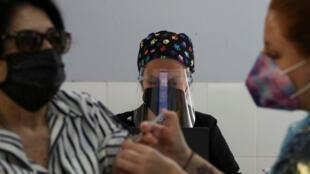 Una mujer recibe una inyección como parte de la campaña de vacunación contra la influenza estacional para niños y ancianos, adicional a la pandemia de la enfermedad por coronavirus, en Santiago de Chile, el 13 de abril de 2021.