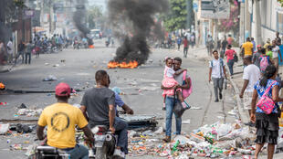 A man carries a child past burning barricades as opponents of Haitian President Jovenel Moise demonstrate on January 15, 2021 in Port-au-Prince to demand his departure from power on February 7, the day they believe to be the last of his term