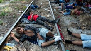 Des migrants, en majorité honduriens, se dirigeant vers les États-Unis se reposent sur la voie ferrée d'Arriaga, dans le sud du Mexique, le 26 octobre 2018.