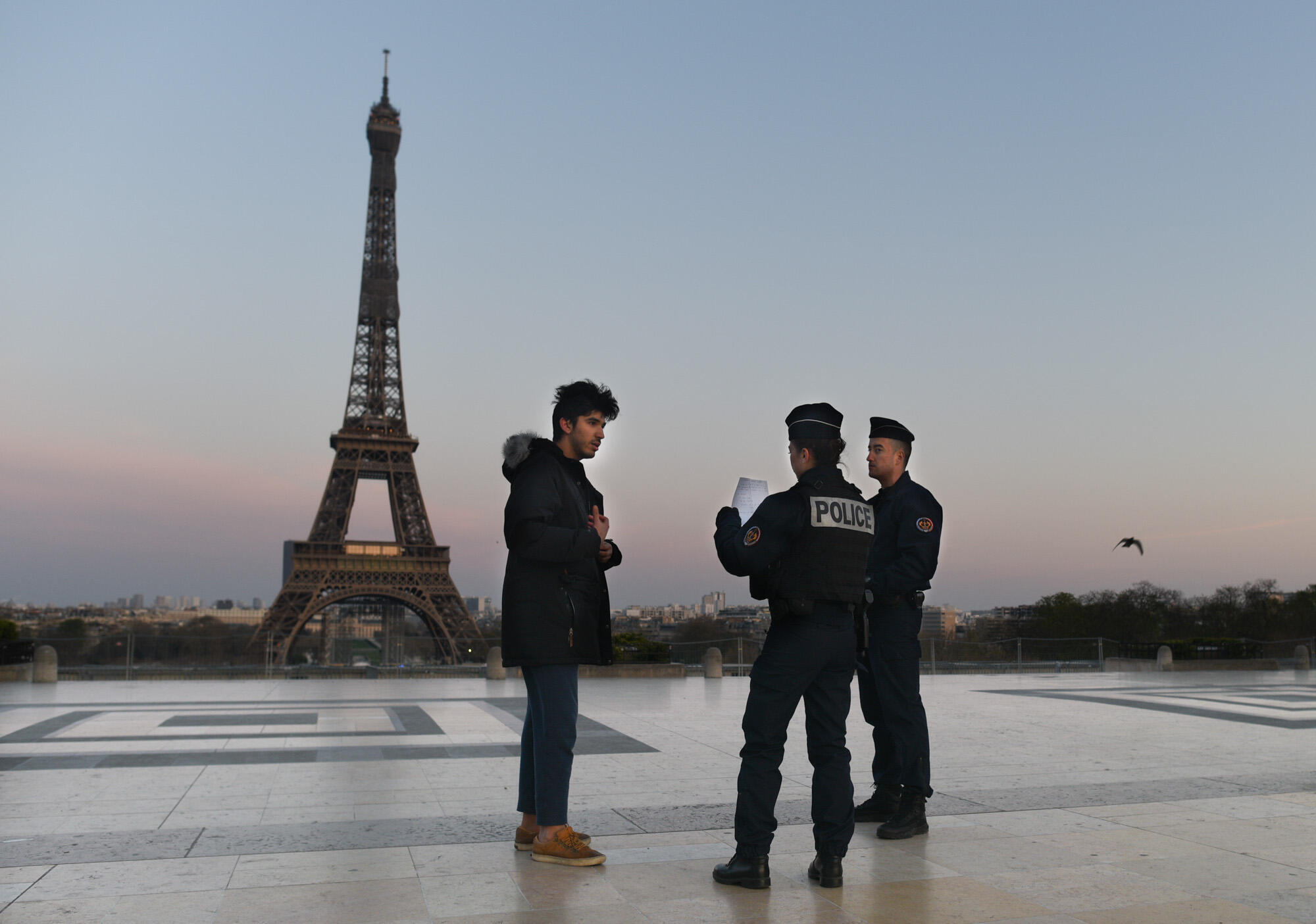 The Trocadero esplanadeoverlookingthe EiffelTower is eerily deserted. Several police officers patrol the windswept square, which is usually teeming with tourists and illegal streetvendors,checking people'spermission forms: Anyone on the streets must now carry a signed document stating their reason for notremainingat home.
