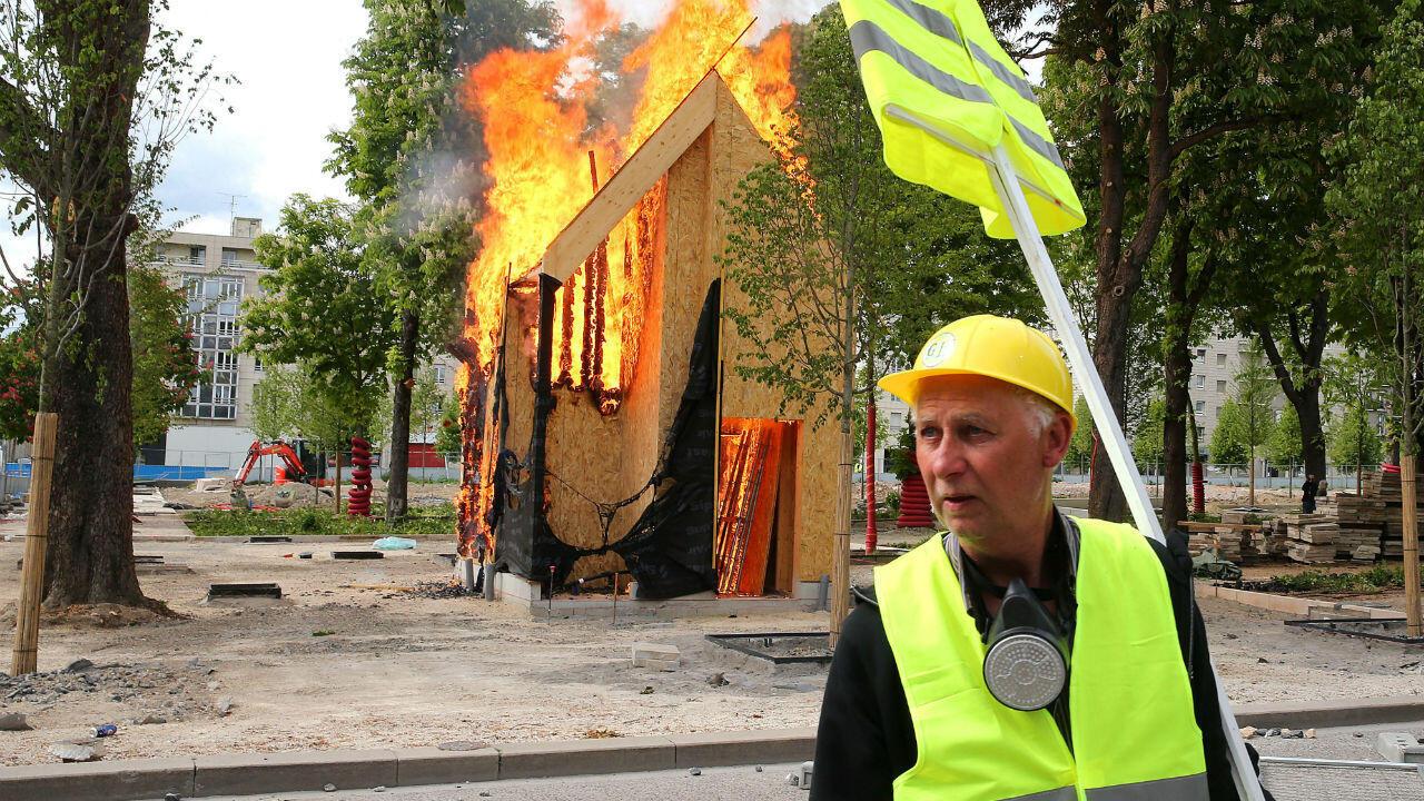 Un hombre se para cerca de una choza en llamas durante una manifestación convocada por el movimiento 'chalecos amarillos' el 18 de mayo de 2019 en Reims, este de Francia.