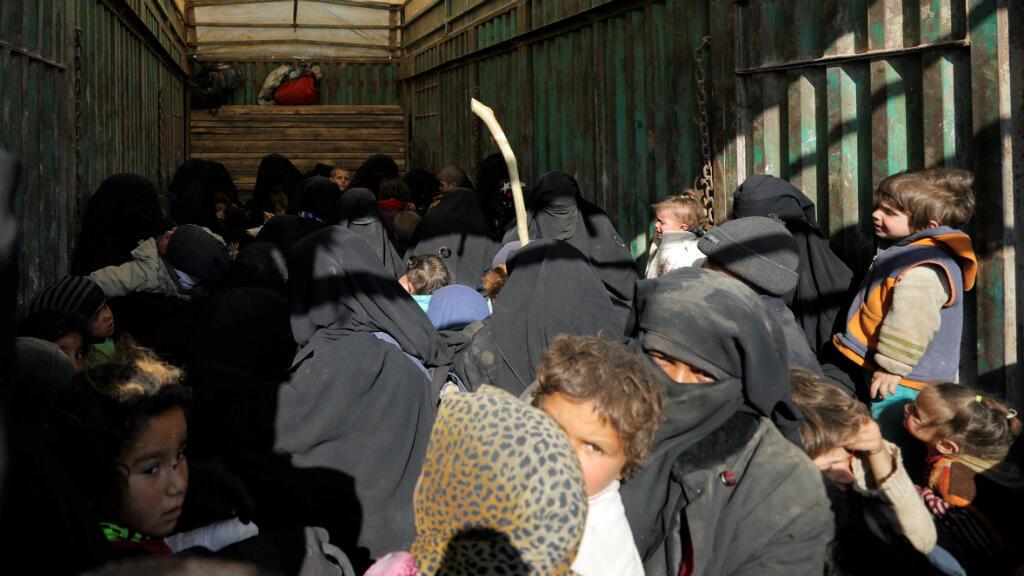 Niños y mujeres están parados en la parte trasera de un camión cerca del pueblo de Baghouz, provincia de Deir Al Zor, Siria, el 20 de febrero de 2019.