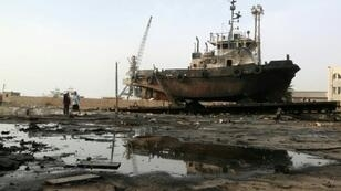 عمال يتفقدون الأضرار في موقع غارة في مرفأ الحديدة في 27 أيار/مايو