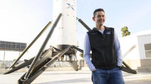 Jared Isaacman, milliardaire et chef de la mission spatiale qui l'emmènera en orbite avec trois autres touristes de l'espace, pose devant le premier étage de la fusée Falcon 9 devant le sièger de SpaceX à Hawthrone (Californie), le 2 février 2021