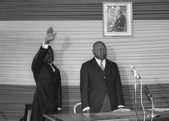 Le vice-président Albert-Bernard Bongo, qui deviendra plus tard Omar Bongo Ondimba, (à g.) prête serment aux côtés du président du Gabon, Leon Mba, lors de la cérémonie de prestation de serment à l'ambassade du Gabon à Paris, le 12 avril1967.