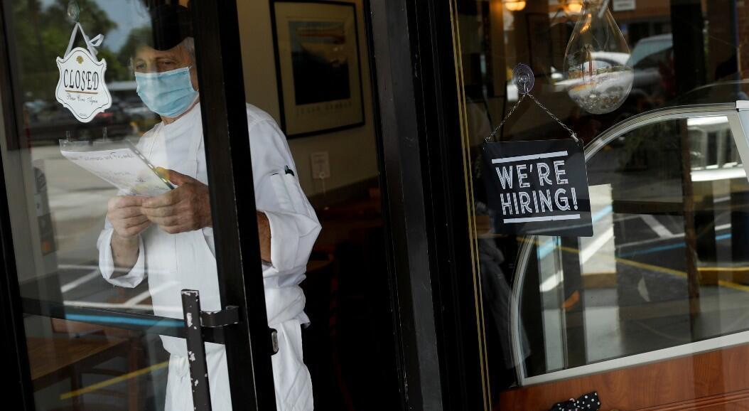 """Un trabajador de un restaurante junto a un anuncio que dice: """"estamos contratando"""", en Miami, Estados Unidos, el 18 de mayo de 2020."""