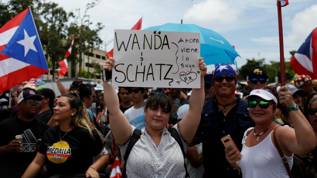"""Una mujer sostiene un cartel que dice """"Wanda y Schatz. Ahora es lo tuyo"""" durante una manifestación para celebrar la renuncia del gobernador puertorriqueño, Ricardo Rossello. San Juan, Puerto Rico, el 25 de julio de 2019."""