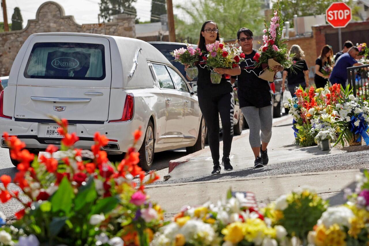 Un par de mujeres llevan flores para un homenaje a las víctimas de un tiroteo en El Paso, Texas, Estados Unidos, el 18 de agosto de 2019.