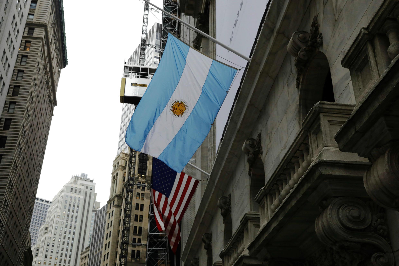 Banderas argentina y norteamerica a media asta al frente de la bolsa de Nueva York, EE.UU., noviembre 1, 2017