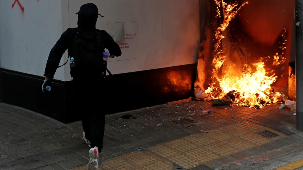 Un manifestante corre frente a el Banco de China, durante la huelga convocada en Hong Kong.