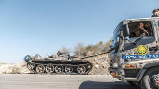 A damaged tank stands abandoned on a road as a truck of the Amhara Special Forces passes by near Humera, Ethiopia on November 22, 2020.